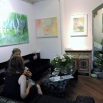 2 Personen in einer Galerie sitzend