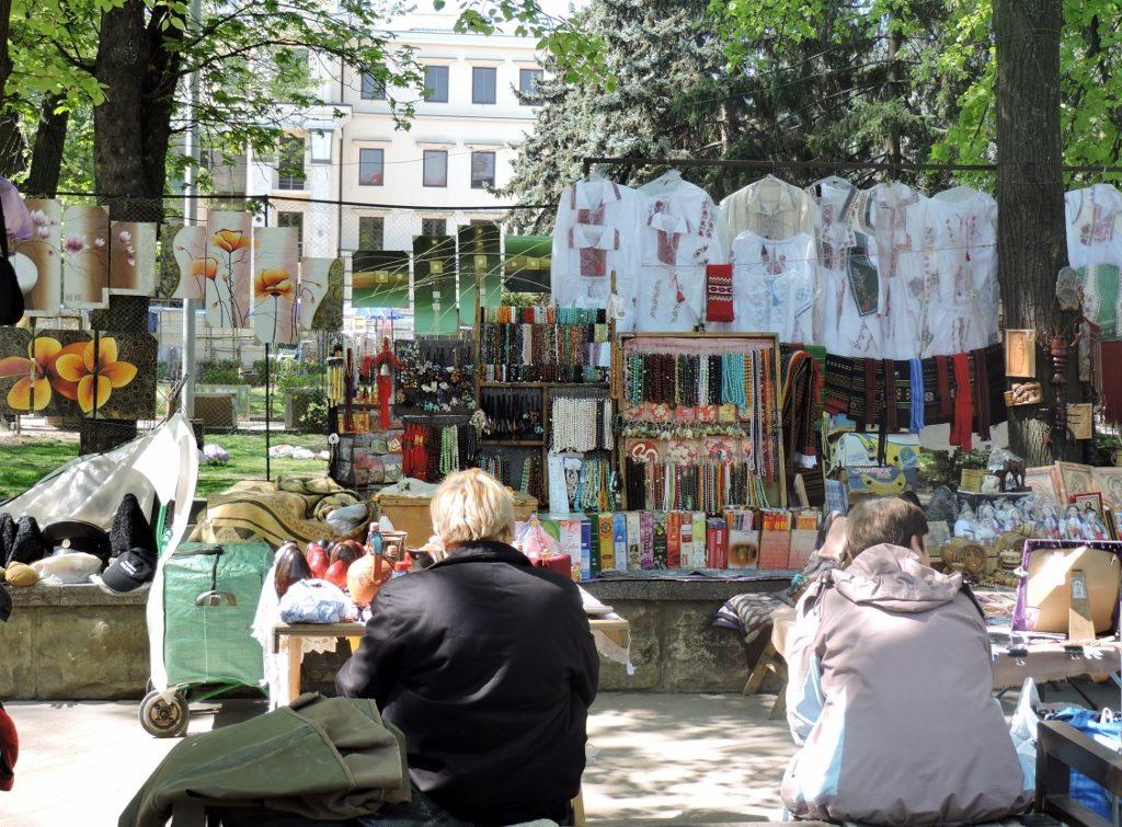 2 Menschen sitzen vor einem Flohmarkt in Chisinau