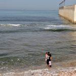 Mann mit Kind am Meeresufer