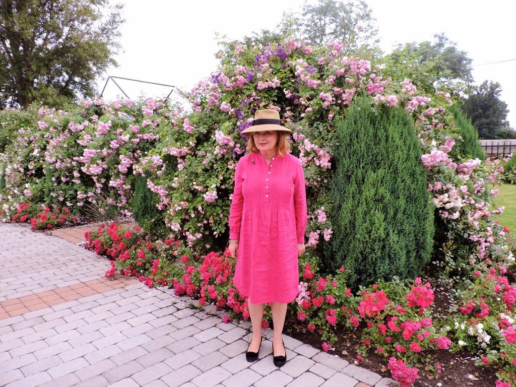 Dame mit Strohhut in pinkem Kleid vor blühenden Sträuchern stehend
