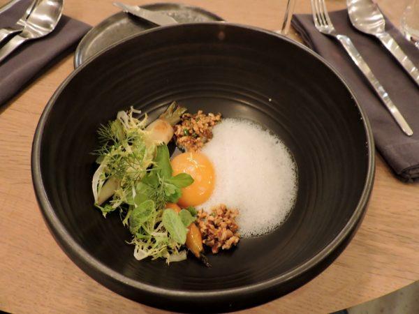 Vorspeise mit Ei in einem schwarzen Teller