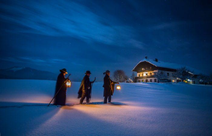 3 Männer unterwegs im Schnee zu einem Haus im Stille Nacht Land