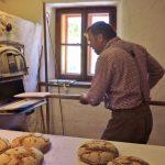 Mann schiebt Brot in Ofen
