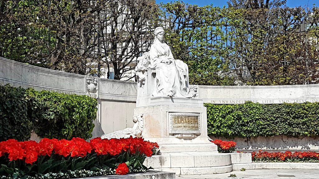 steinernes Frauen Denkmal mit roten Blumen