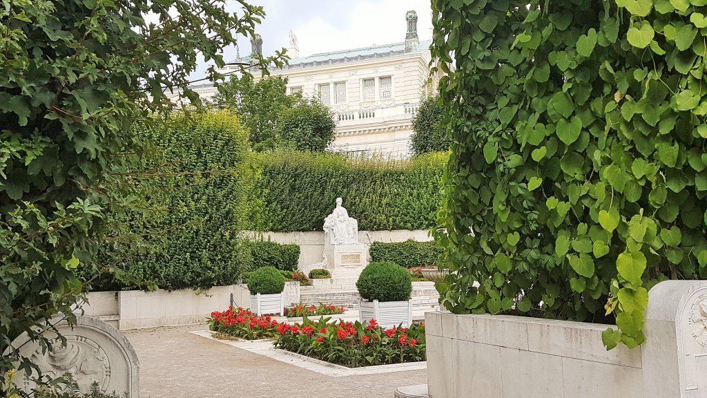 weißes Denkmal versteckt hinter grünen Ranken