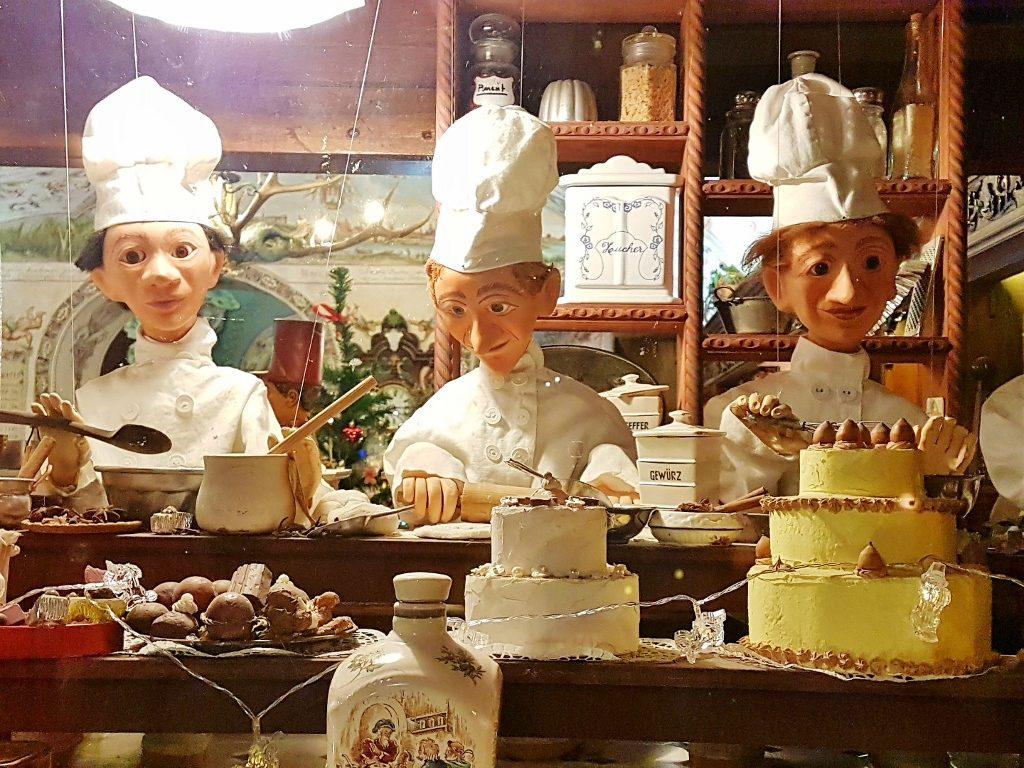 3 Puppen als Köche angezogen im Schaufenster