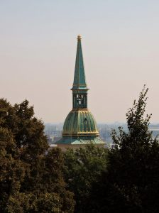 Kirchturmspitze zwischen Bäumen