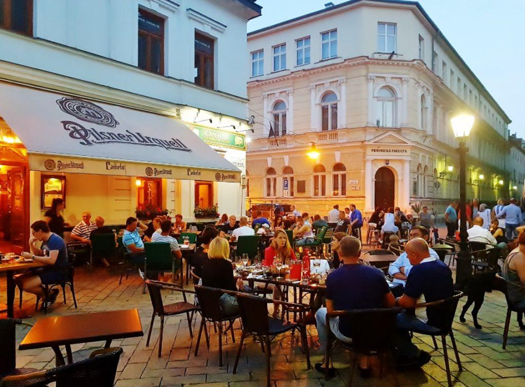 Lokale mit Gästen im Freien am Abend
