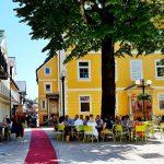 gelbes Haus mit Baum und Menschengruppe davor