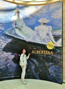 Ausstellungs-Plakatwand mit Frau davor stehend