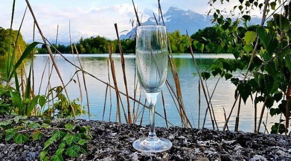 Sektglas auf einer Mauer mit Seeblick