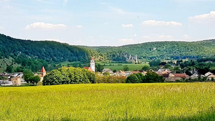 grüne Hügellandschaft mit Dorf