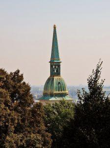 Kirchturmspitze hinter Bäumen, mit der Bratislava Card entdecken