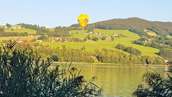 Gelber Heißluftballon über einer Seenlandschaft