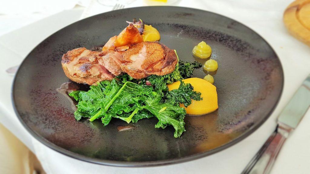 Fleischgericht mit Gemüse auf schwarzem Teller