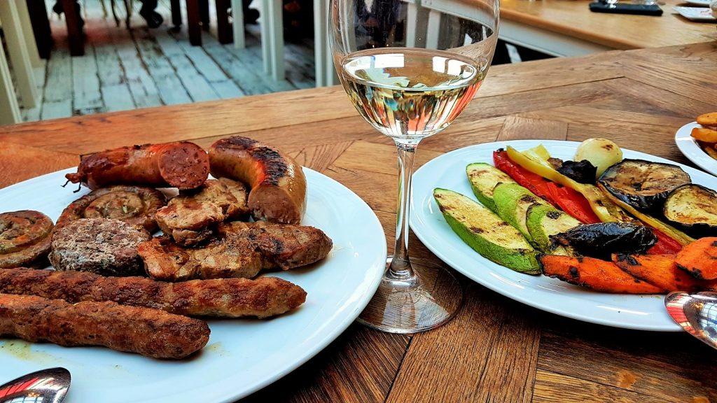 Würste und gegrilltes Gemüse auf Teller und Weinglas