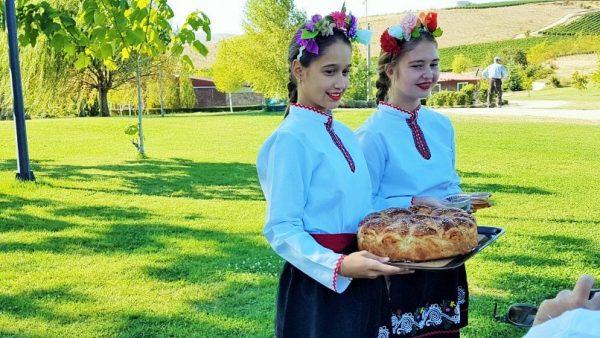 zwei bulgarische Mädchen in Tracht offerieren Gebäck auf einem Tablett