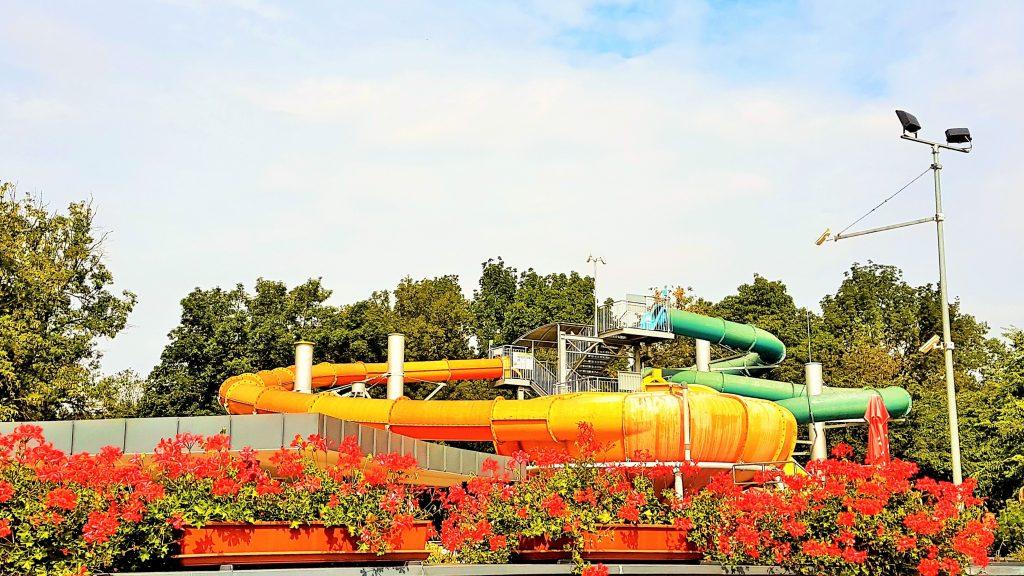 Bükfürdö Therme mit großer Wasserrutsche und roten Blumen im Vordergrund