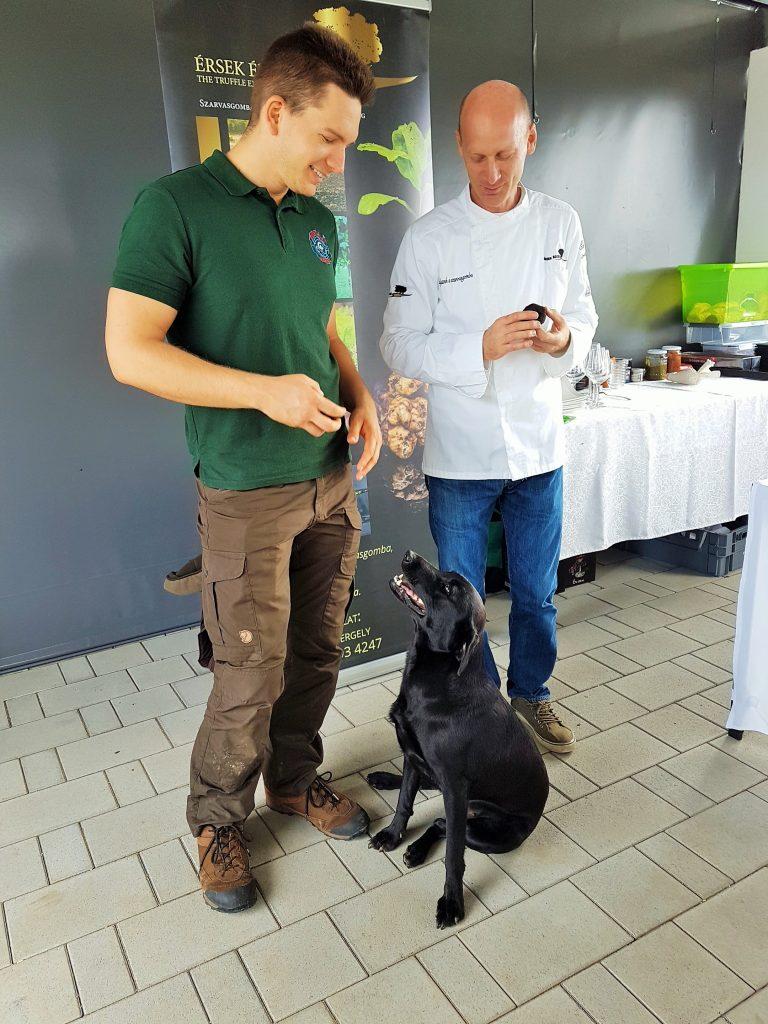 zwei Männer mit einem Labrador Hund