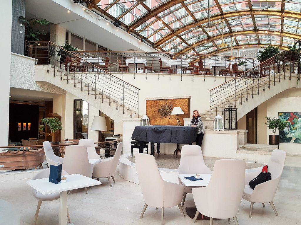 stilvolle Hotellobby in hellen Farben mit Glasdach und Klavier im Mittelpunkt