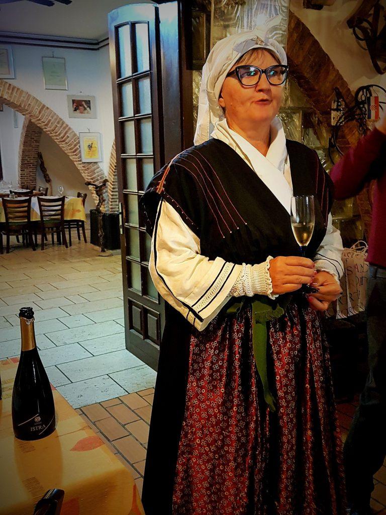 Frau in slownischer Tracht gekleidet mit Sektglas in der Hand, slowenische Riviera