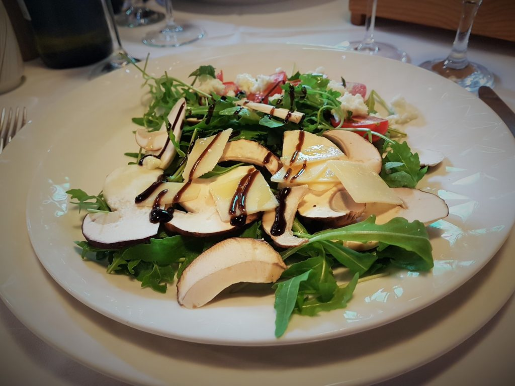 Ruccola Salat mit Steinpilzen auf Teller