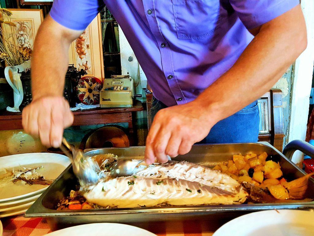 ein Mann filetiert Fisch in einer Pfanne