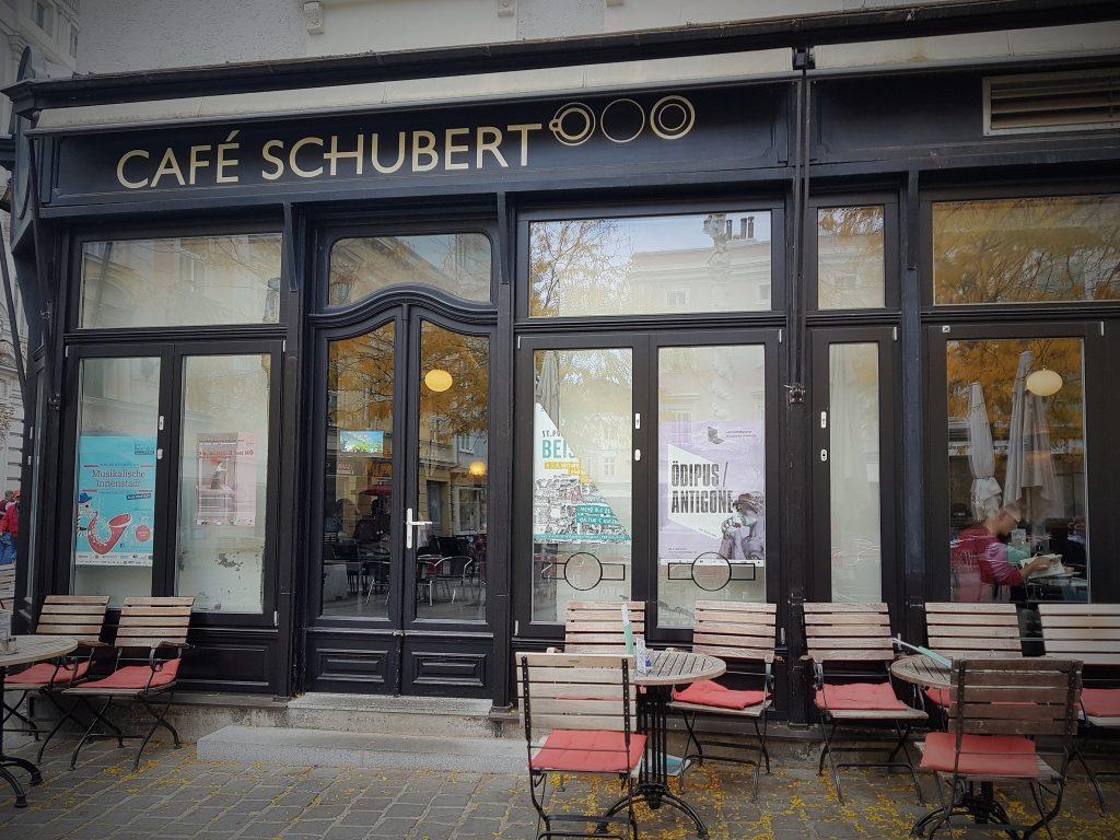 nettes Café mit Stühlen vor dem Eingang zum sitzen