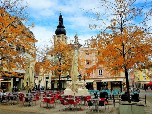 schöner Altstadt-Platz unter herbstlich gelben Bäumen mit Café im Freien