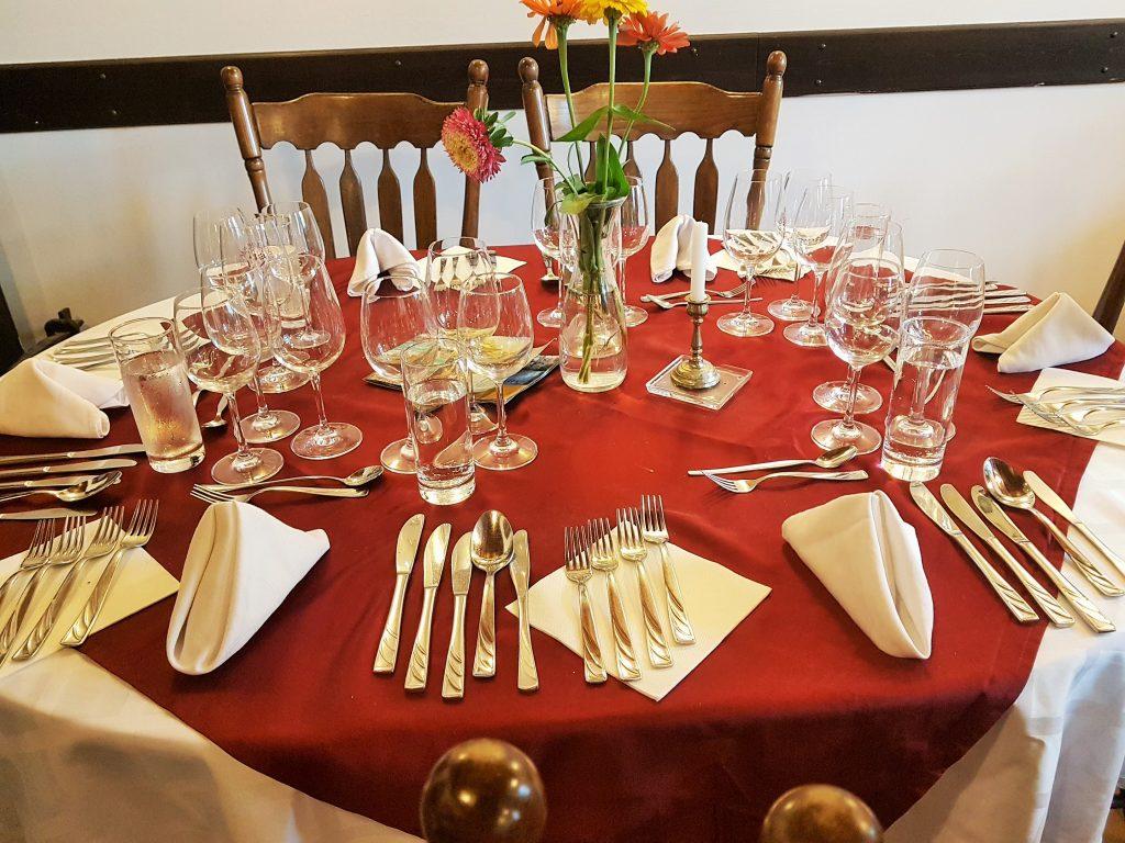 schön gedeckter Tisch mit roter Decke und Gläsern in Slow Food Restaurant