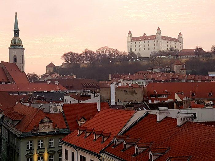 Blick über rote Dächer auf die Burg Bratislava
