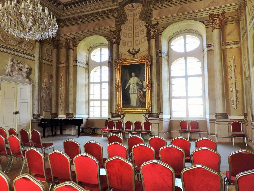 ein historischer Konzertsaal mit roten Stühlen