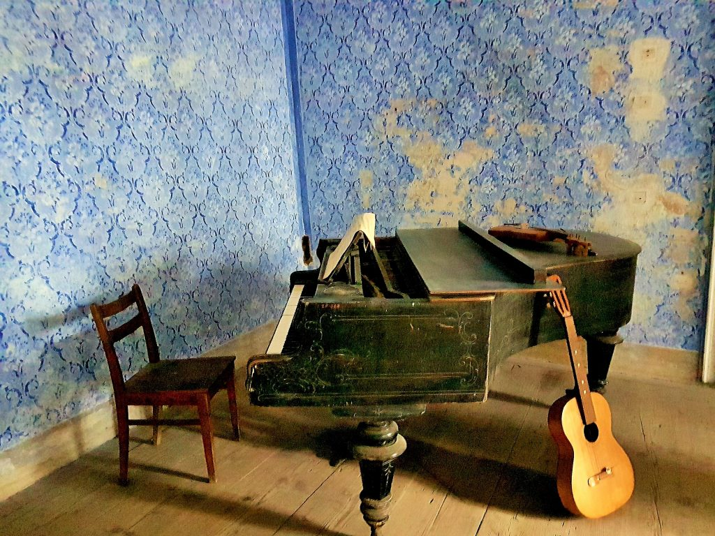 ein altes Piano, Gitarre und Stuhl im Raum mit desolater Tapete an der Wand