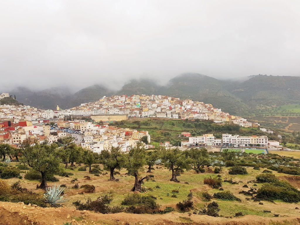 malerischer Ort auf einem Hügel mit tiefhängenden Wolken darüber