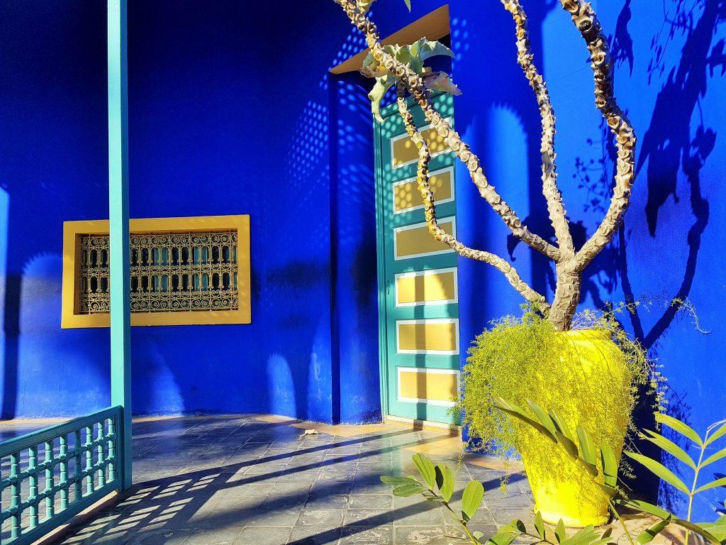 kobaltblaue Fassade mit gelbem Pflanzentopf