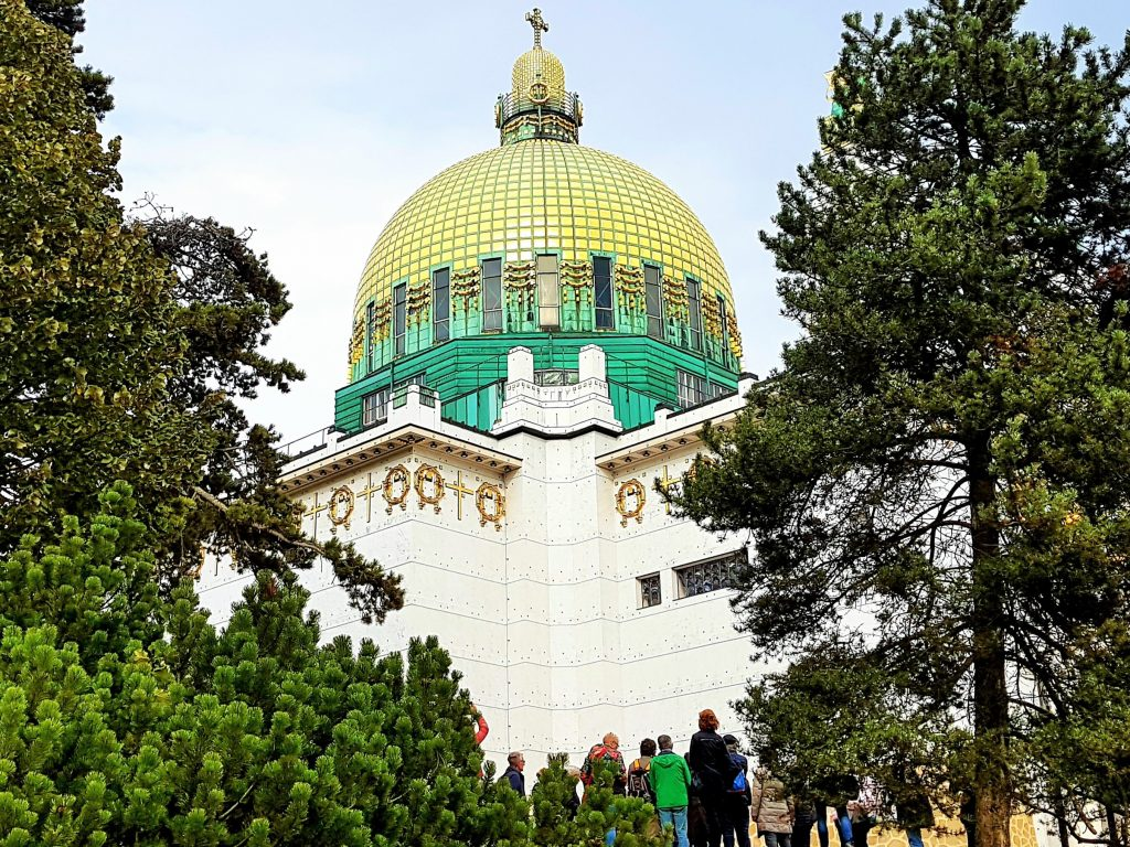 goldene Jugendstil-Kuppel zwischen grünen Bäumen