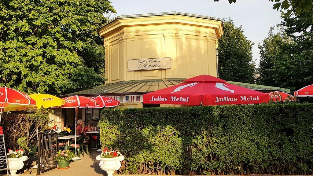 Park-Café im Grünen mit roten Sonnenschirmen