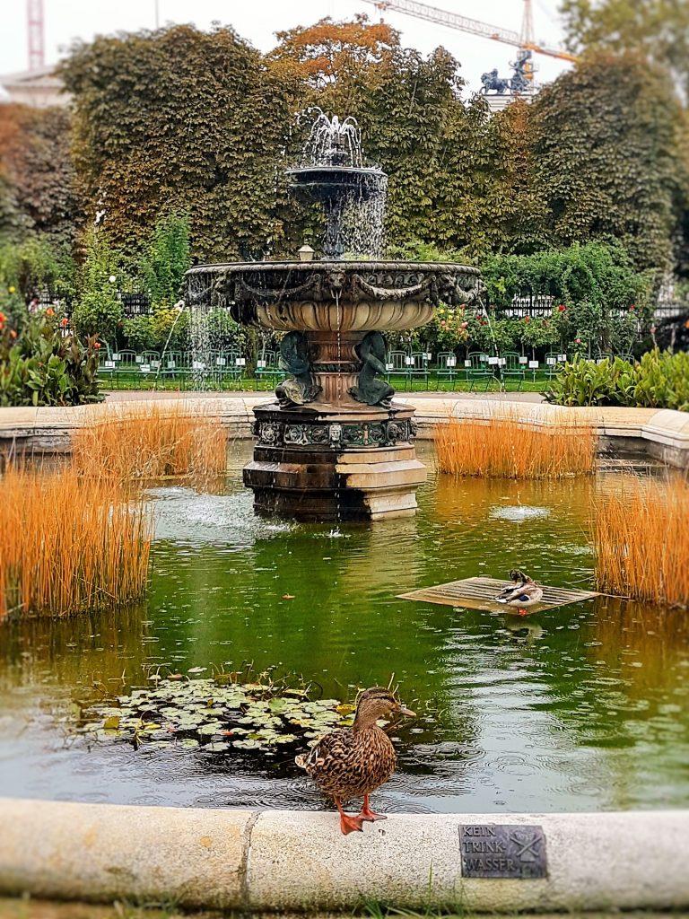 Brunnen mit Ente am Rand sitzend