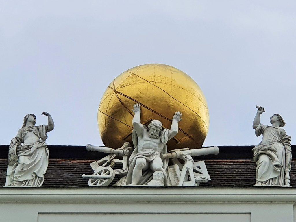 Skulptur, Atlas trägt eine goldene Weltkugel