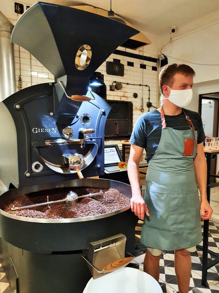 Kaffee-Rösterei mit Eigentümer neben Röstmaschine