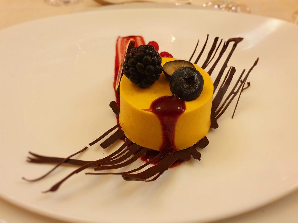 rundes Dessert mit Schokolade-Frucht-Dekoration