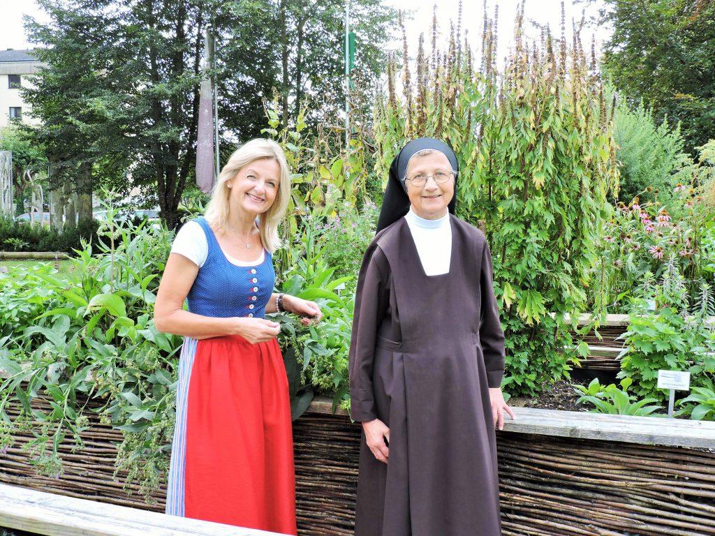 Nonne u. Frau im Dirndl im Garten
