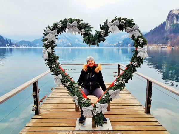 Reisebloggerin steht inmitten eines großen Herzen am See-Steg