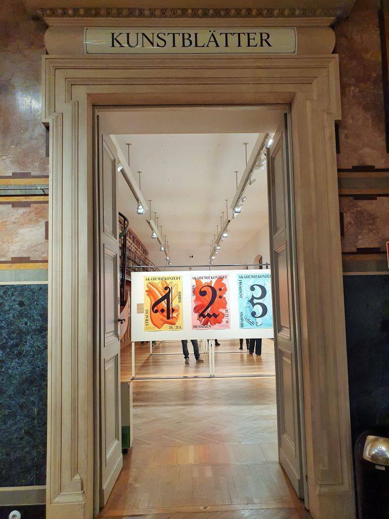 Saal-Eingang mit Blick auf Raum mit Plakaten