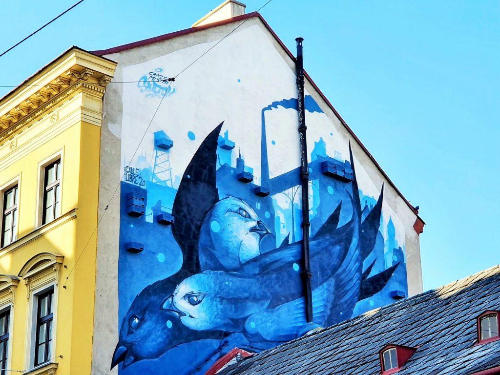 Streetart Mural an Häuserfassade mit blauen Vögeln