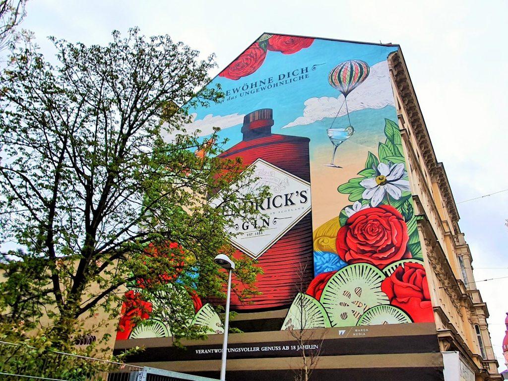 großes Streetart Mural bunt mit Baum davor