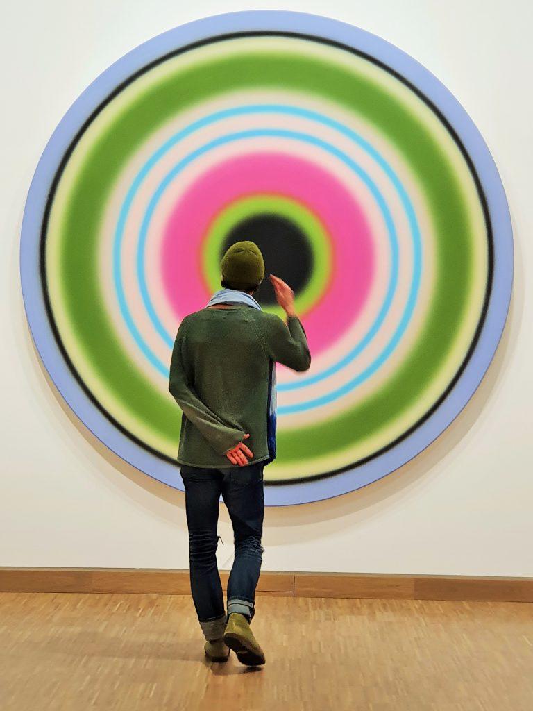 ein junger Mann steht vor einem geometrisch abstrakten Gemälde