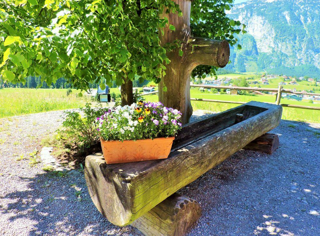ländlicher Holzbrunnen mit Blumenschmuck
