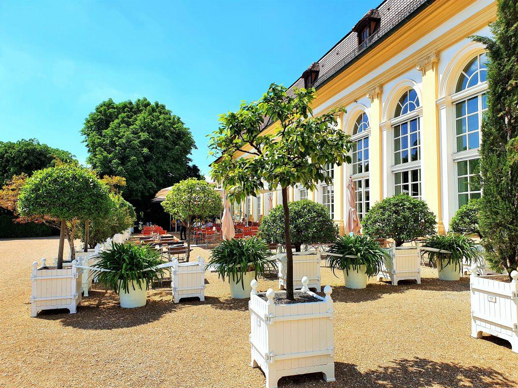 Garten-Restaurant im Freien vor einer Orangerie
