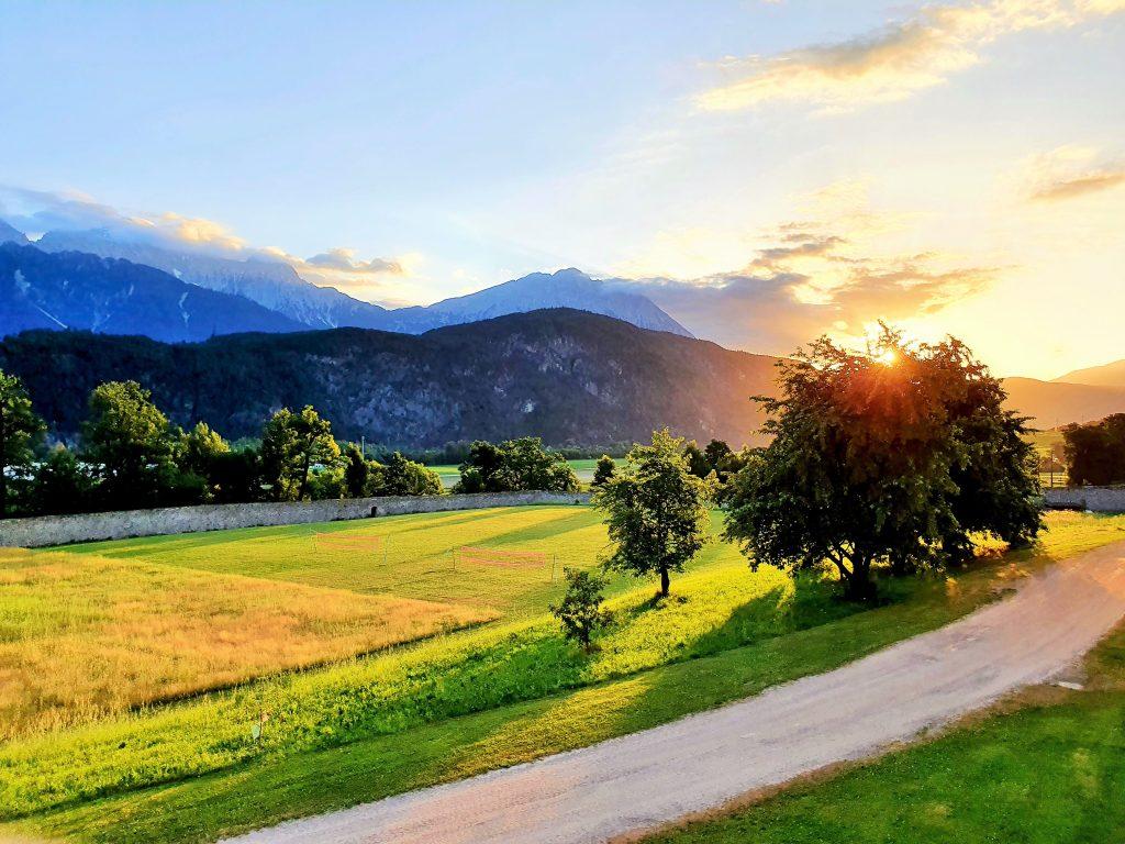 Sonnenaufgang über sommerliche Landschaft mit Tiroler Bergen